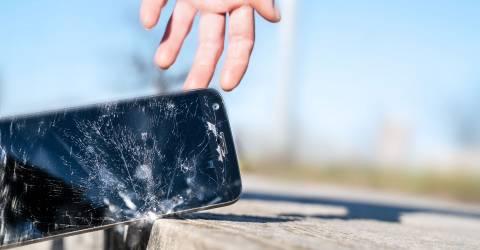 Een mobiele telefoon die op de stenen kapot valt